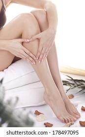 Perfect female legs. Woman applying moisturizer.