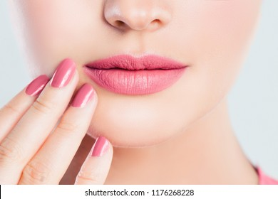 Perfect female lips closeup. Pink lips makeup and manicured nails with pink nail polish