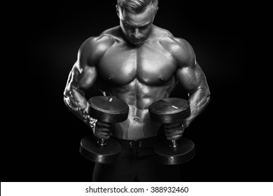 Perfect fit athletic guy workout with dumbbells, perfect abs, shoulders, biceps, triceps and chest isolated on dark background. Black and white photo.