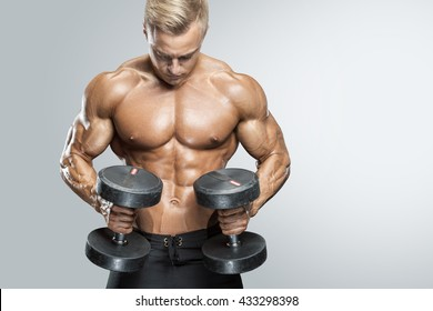 Perfect fit athletic guy workout with dumbbells, perfect abs, shoulders, biceps, triceps and chest. Fitness muscular body isolated on white background.