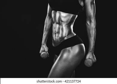 Perfect Fitness Body of Beautiful Woman in Drops. Fitness-instructor in Sports Clothing. Female Model with Fit Muscular and Slim Body in Sportswear. Young Fit Girl Lifting Dumbbells. CloseUp