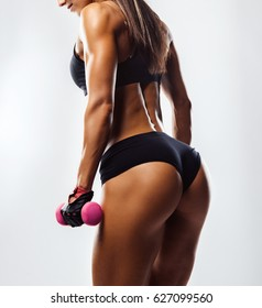 Perfect Fitness Body of Beautiful Woman. Fitness Instructor in Sports Clothing. Female Model with Fit Muscular and Slim Body in Sportswear doing Workout. Young Fit Girl Lifting Dumbbells. Back View