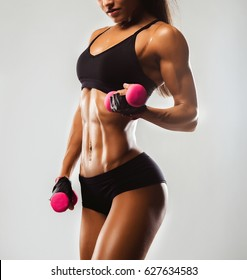 Perfect Fitness Body of Beautiful Woman. Fitness Instructor in Sports Clothing. Female Model with Fit Muscular and Slim Body in Sportswear. Young Fit Girl Lifting Dumbbells