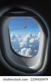 Perfect fluffy clouds out the plane window on sunny, blue sky day