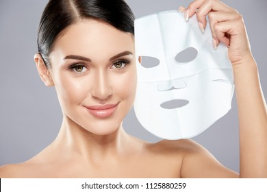 Perfect girl with dark hair, big eyes, dark eyebrows and naked shoulders looking at camera, a model with light nude make-up, using facial mask.