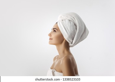 Perfect girl with naked shoulders, wearing white towel on head and body looking forward, a model with light nude make-up standing on white studio background, beauty photo, profile portrait. Side view.