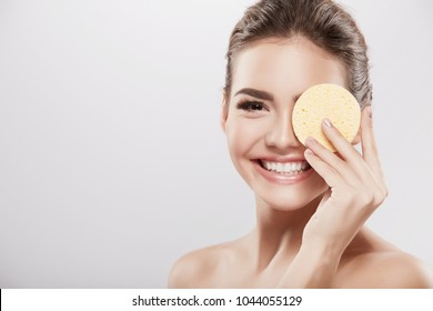 Perfect girl with nude make up and naked shoulders posing at grey background with cleaning sponge, skin care concept, beauty photo, close up portrait.
