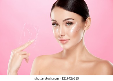 Perfect girl with nude make up and naked shoulders at studio background, invisible eye patches on face, skin care concept, looking at camera, holding pack of eye patches.