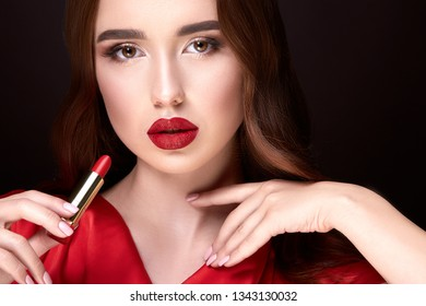 Perfect girl in red wearing evening make up with red lips and long lashes at studio background, close up portrait, holding lipstick.