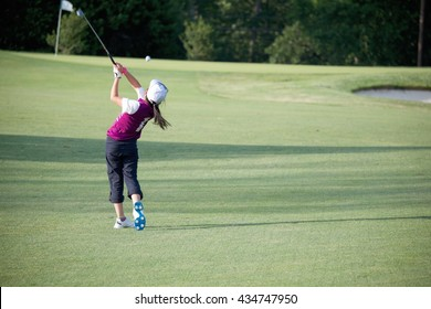 PERFECT GOLF SWING BY A 9 YEARS OLD GIRL PLAYING IN PGA JUNIOR LEAGUE GOLF / APPROACH SHOT FROM FAIRWAY WITH 8 IRON RIGHT ON TARGET( FLAG , PIN ) / MARYLAND / USA