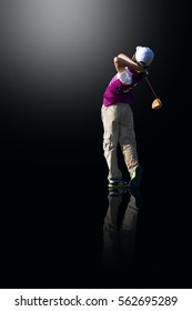 PERFECT GOLF SWING BY A 9 YEARS OLD BOY PLAYING IN JUNIOR LEAGUE GOLF / TEE OFF SHOT WITH DRIVER / ISOLATED ON BLACK BACKGROUND WITH REFLECTION ON GROUND