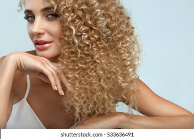 Perfect Hair. Beautiful Woman Model With Long Healthy Blonde Curly Hair. Portrait Gorgeous Sexy Girl With Natural Facial Makeup, Beauty Face And Fashion Hairstyle. Hair Care Cosmetics. High Resolution