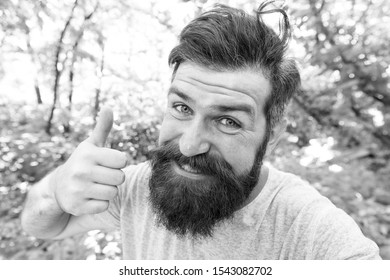 Perfect hair length for his face shape. Happy man with styled hair giving like hand. Hairy guy with stylish mustache and beard hair on summer nature. Bearded hipster smiling with unshaven face hair.