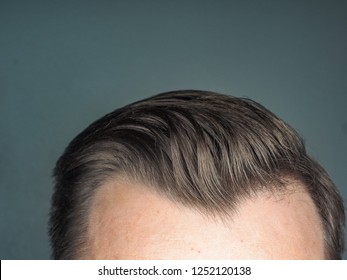 Perfect hairdo on male towards gray background with copy space