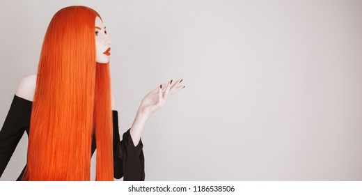 Perfect halloween attire. Gothic redhead woman with perfect straight hair in black dress advertise product. Redhead girl with red lips. Gothic look. Hair straightening in salon. Cosmetics advertise