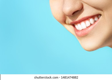 Perfect healthy teeth smile of a young woman. Teeth whitening. Dental clinic patient. Stomatology concept. Isolate on a blue background