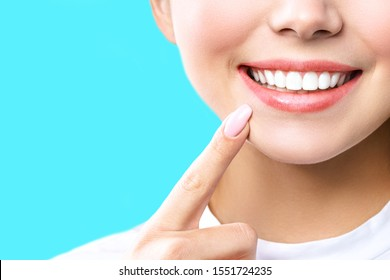 Perfect healthy teeth smile of a young woman. Teeth whitening. Dental clinic patient. Image symbolizes oral care dentistry, stomatology. blue Background.