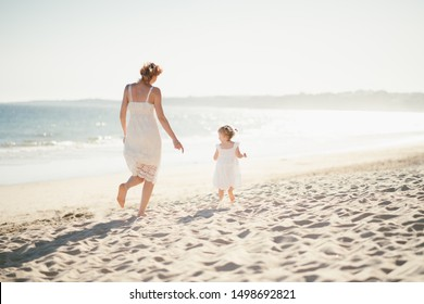 Perfect holidays. Mother and daughter on the beach near ocean walking and having fun. Family vacation concept.