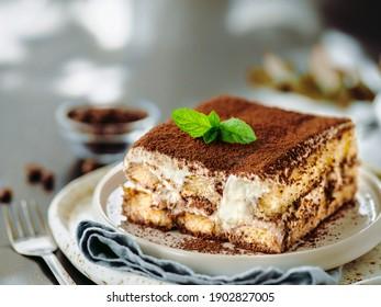 Perfect homemade tiramisu cake with fresh mint. Tiramisu portion on plate over gray background. Delicious no bake tiramisu ready-to-eat. Close up. Copy space