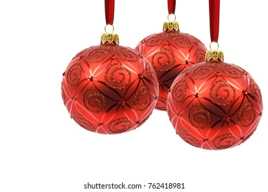 Perfect and ideal three red Christmas balls hanging on a red ribbon on a white background in close-up