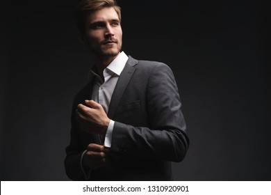 Perfect to the last detail. Handsome young businessman adjusting his sleeves while standing against gray background