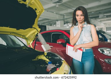 Perfect lines. The young dark-haired woman examining car at the dealership and making his choice. Horizontal portrait of a young female model at the car. He is thinking if he should buy it