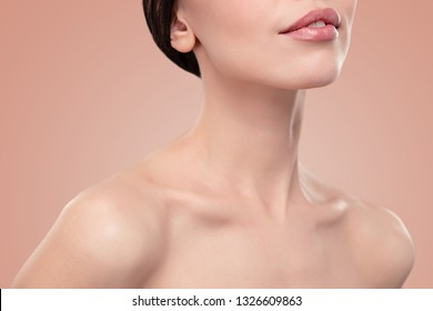 Perfect Lips. Sexy Girl Mouth and shoulders close up. Beauty young woman Smile. Natural plump full Lip. Lips augmentation. Beautiful clavicles. Close up detail on beige background isolated