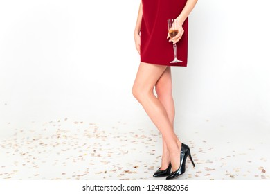 Perfect long legs of young woman in elegant dresses having fun, smiling, dancing and drinking champagne in studio on white background. Christmas party celebration concept.