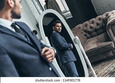 Perfect look. Reflection of handsome young man in full suit adjusting his jacket while standing in front of the mirror indoors