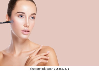 Perfect Makeup. Highlighting. Beautiful Young Woman applying Highlighter on Cheekbone. Beauty Fashion. Cosmetic Eyeshadow. Blush. peach background with copy space