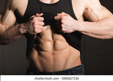 Perfect man shows his six pack abs. Muscular and fit torso of young male. Hunk with athletic body holding shirt, striptease.
