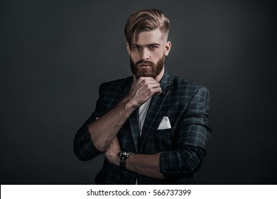 Perfect man. Young hipster holding hand on chin and looking at camera while standing against grey background