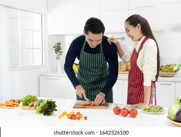 Perfect marriage couple cooking and preparing ingredient in kitchen at home. wife looking at husband cutting vegetables for salad. white background - copy space.