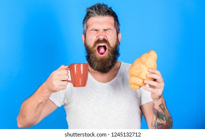 Perfect match. Man start morning with cup of coffee and fresh croissant. Morning tradition concept. But first coffee. Enjoy every sip of coffee. Bearded hipster enjoy breakfast drink coffee.
