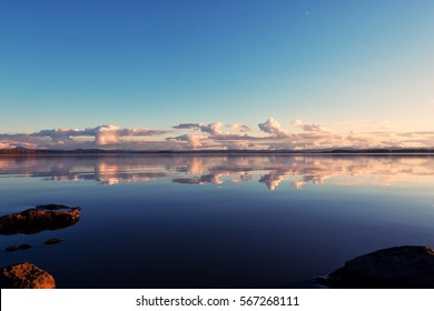 Perfect mirror image of clouds reflected in the rich, deep blue waters of a lake in Oregon. Featuring rocks in the foreground colored by the setting sun.