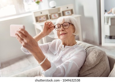 Perfect mood. Cheerful senior woman sitting on the sofa and smiling at the camera, adjusting her eyeglasses, while taking selfie in her living room