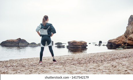 Perfect morning. Back view of strong and confident disabled woman in sportswear with prosthetic leg is standing on the beach and keeping arms on her hips.