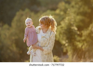 Perfect motherhood, mother and daughter stroll in the autumn forest, learn to take the first steps