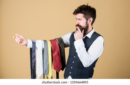 Perfect necktie. Select tie that has colors of your suit and shirt as well as at least one other color to provide an accent. Man bearded hipster hold few neckties. Guy with beard choosing necktie.