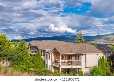 A perfect neighborhood. Houses in suburb at Summer in the north America. Top of a luxury house with nice window over blue and white sky.