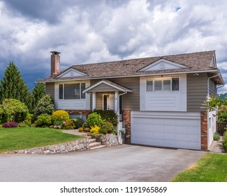 A perfect neighborhood. Houses in suburb at Summer in the north America. Fragment of a luxury house with nice window over dramatic cloudy sky.