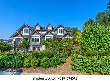 A perfect neighborhood. Houses in suburb at Summer in the north America. Fragment of a luxury house with nice windows over blue sky.