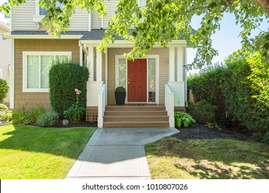 Perfect neighbourhood. Door steps and concrete pathway leading to residential house main entrance with flower pot under the porch