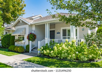 Perfect neighbourhood. Entrance of residential house with concrete pathway and blossoming flowers in front of the house. Family house on bright sunny day