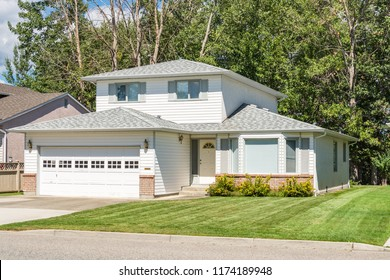 A perfect neighbourhood. Family house with landscaped front yard on sunny day in British Columbia