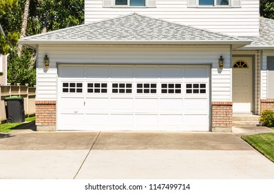 A perfect neighbourhood. Family house with wide garage door and concrete driveway in front