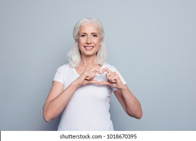 Perfect, nice, aged, old, pretty woman, lover in t-shirt making, showing heart figure with fingers, looking at camera, celebrating woman's day, standing over gray background