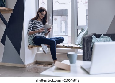Perfect place to work. Attractive young woman using digital tablet while sitting on the window sill