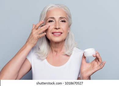Perfect, pretty, woman applying eye cream, holding jar of cosmetic product looking at camera over gray background