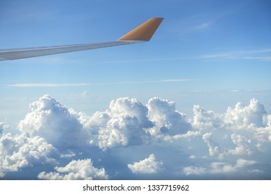 Perfect Puffy clouds from above, with Yellow Plane Wing on Clear Blue Day